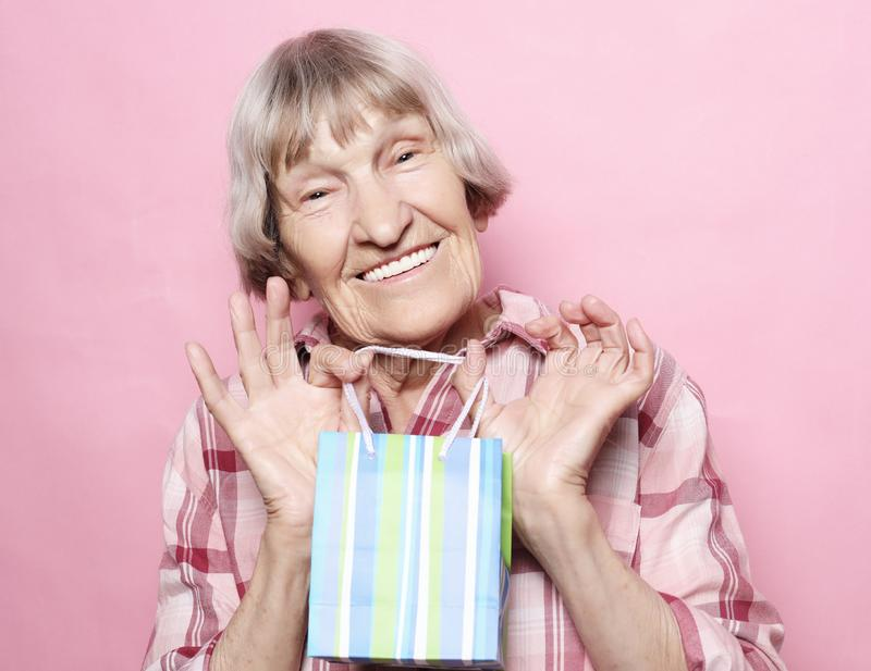 Styl życia i ludzie pojęć: Szczęśliwa starsza kobieta z torba na zakupy nad różowym tłem obrazy stock