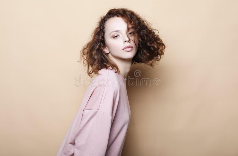 Styl życia, piękno i ludzie pojęć: Młoda śliczna uśmiechnięta kędzierzawa dziewczyna jest ubranym menchii ubrania zdjęcia royalty free