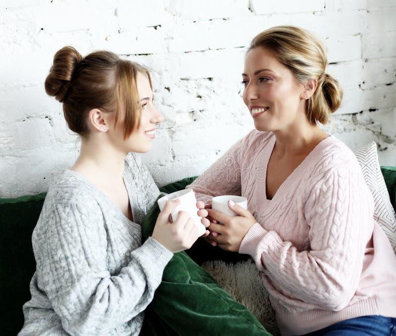 Styl życia, rodzina i ludzie pojęć: Dwa pięknej kobiety matka i córki obsiadanie na kanapie w domu obrazy royalty free
