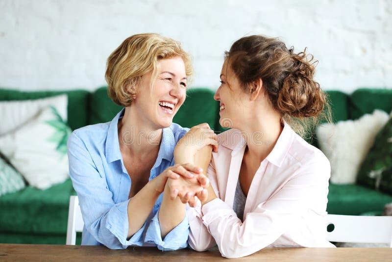 Styl życia, rodzina i ludzie pojęć: Szczęśliwa młoda kobieta i jej matka w domu obraz stock