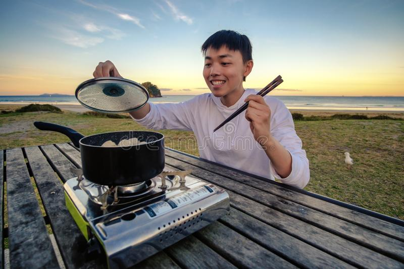 Styl życia wizerunek młody szczęśliwy azjatykci mężczyzna je gorącą garnek kuchenkę na stole plenerowym wzdłuż plaży Czas wolny a zdjęcie royalty free