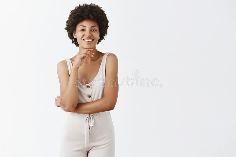 Styl jest w krwi Szczęśliwa i atrakcyjna afrykanina Ameryka kobieta dotyka podbródek z kędzierzawą fryzurą w szarych kombinezonac obrazy royalty free