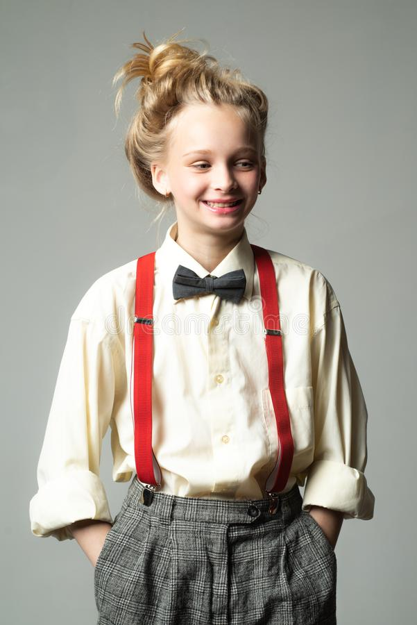 Style in action. teen girl in retro male suit. retro fashion model. vintage charleston party. vintage english style. Suspender and bow tie. old fashioned child stock photography