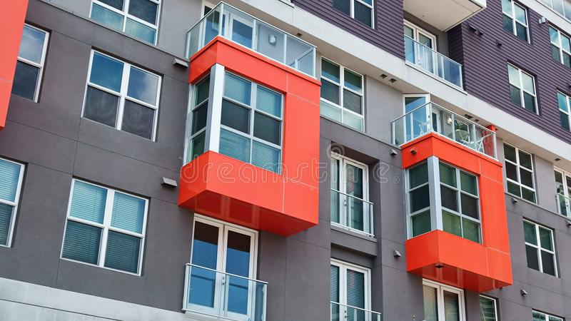 A pair of red pop out bay windows in a modern high rise residential building. Style of architecture representing the modern era of building and design of facades stock images