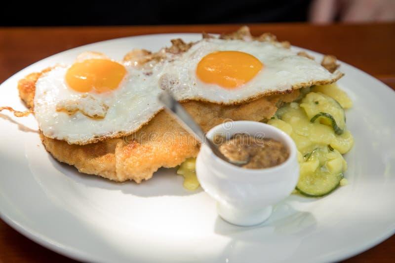 Style de Hambourg d'escalope de veau de viande de porc avec les oeufs au plat, la salade de concombre de pomme de terre et la mou photos stock