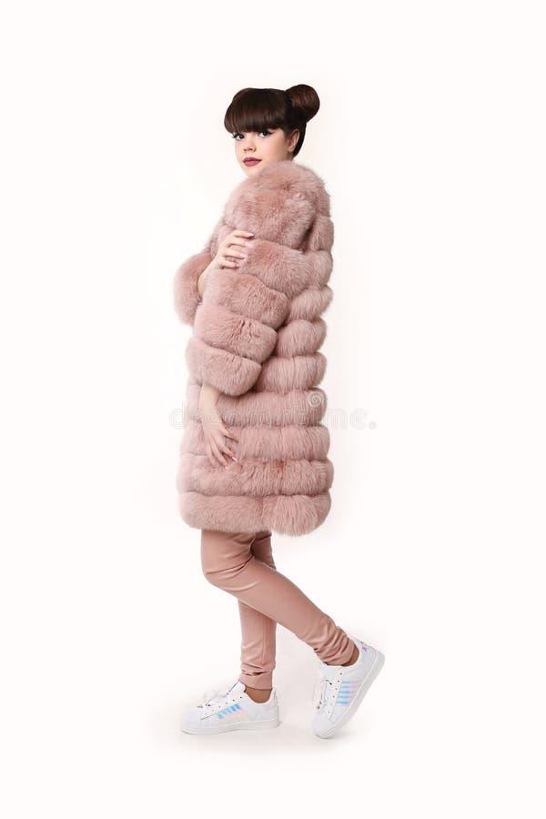 Style de l'adolescence de regard de studio de mode dans le manteau de fourrure rose et des chaussures à la mode photographie stock libre de droits