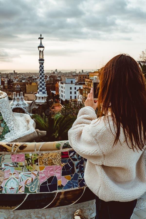 Style de signature de Barcelone femme de touristes moderne dans le manteau au parc de Guell à Barcelone image stock