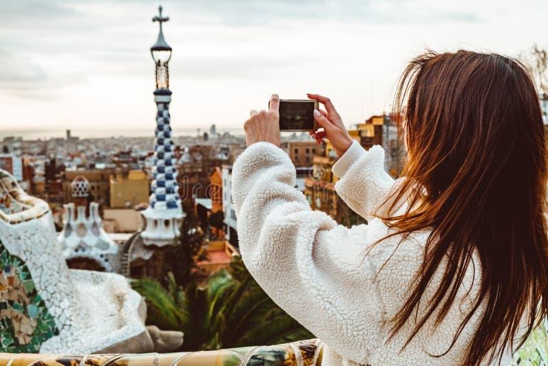 Style de signature de Barcelone femme de touristes moderne dans le manteau au parc de Guell ? Barcelone photos libres de droits
