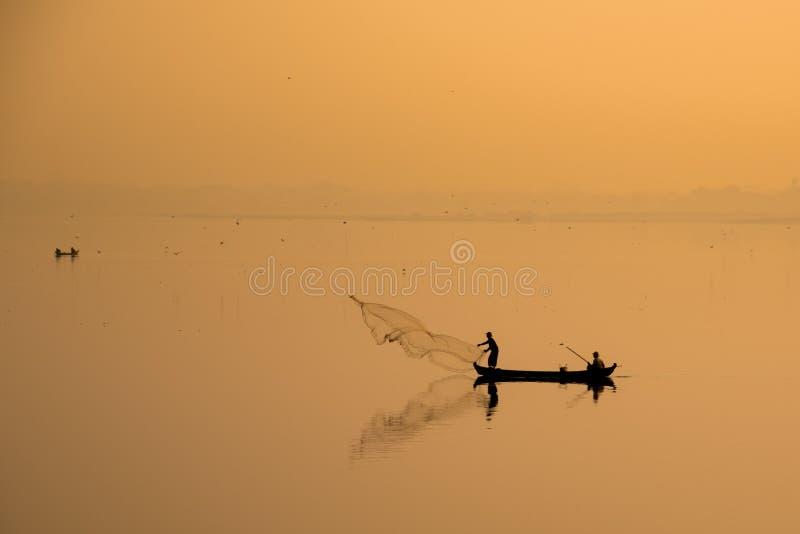 Style de vie asiatique : pêcheur jetant un filet dans le lac sur le lever de soleil, rural en Thaïlande photographie stock libre de droits