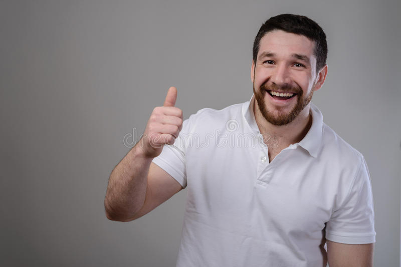 Style de vie et concept de personnes : T-shirt blanc de port d'homme bel heureux montrant des pouces au-dessus de fond d'isolemen photographie stock libre de droits
