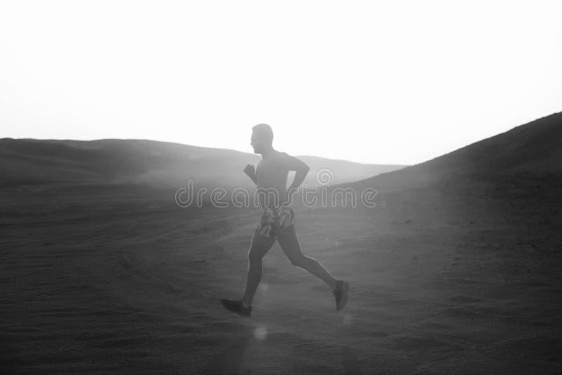 Style de vie sain Coureur d'homme fonctionnant en dune au coucher du soleil photographie stock