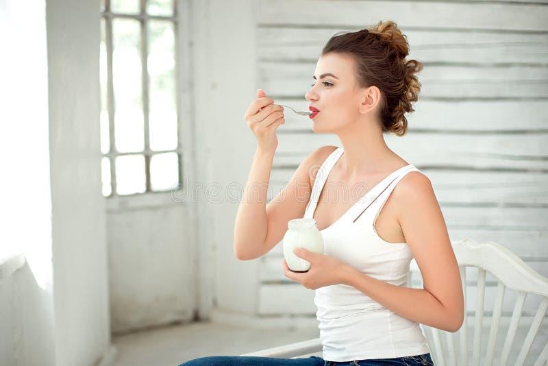 Style de vie sain Portrait de femme de sourire goûtant le yaourt organique frais se reposant dans la pièce lumineuse blanche, por photo libre de droits
