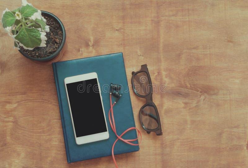 Style de vintage, téléphone intelligent blanc avec l'espace vide noir sur l'écran, verres écouteurs et carnet sur le fond en bois photographie stock