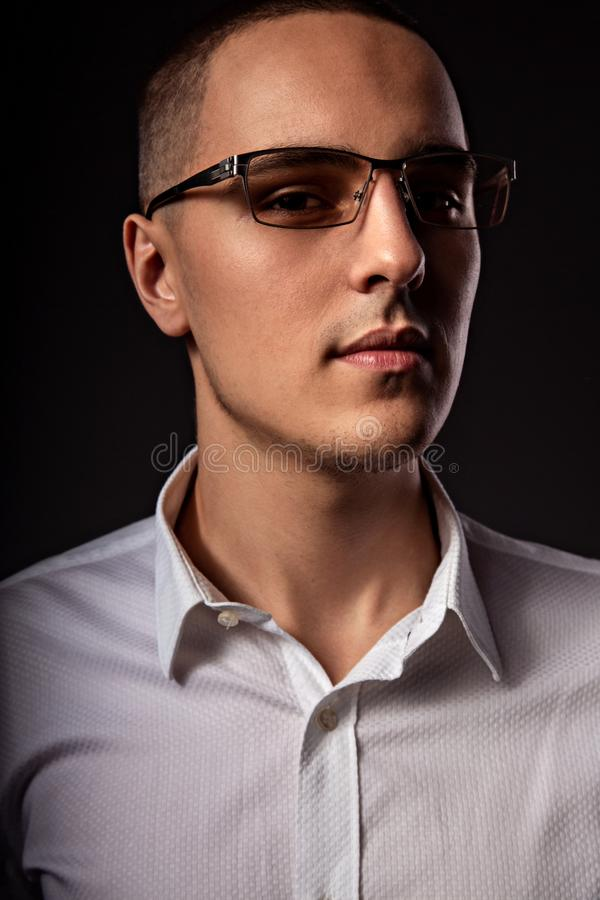 Style elegant young business man in eye glasses looking sreious and arrogant on dark shadow background. Closeup. Art portrait royalty free stock photos