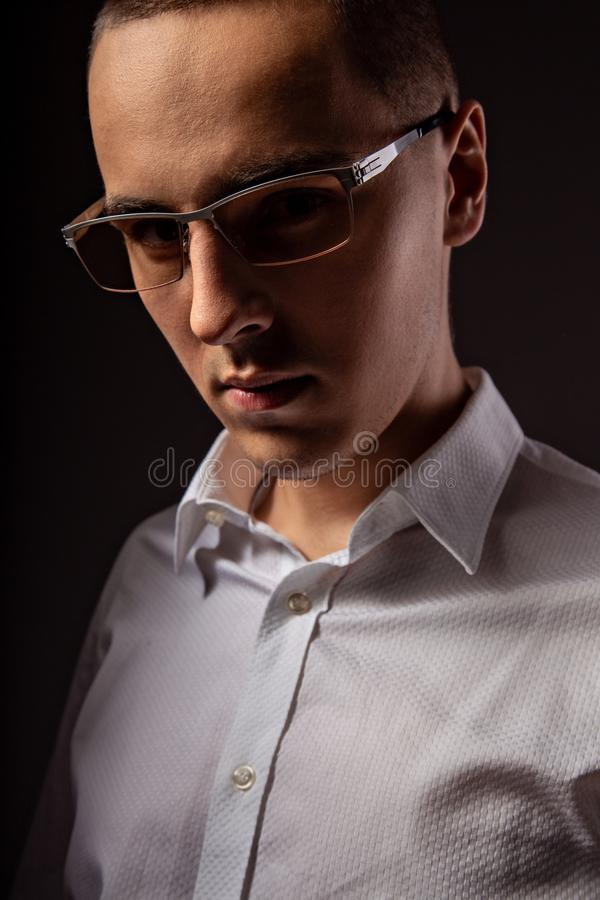 Style elegant young business man in eye glasses looking sreious and arrogant on dark shadow background. Closeup. Art portrait stock photography