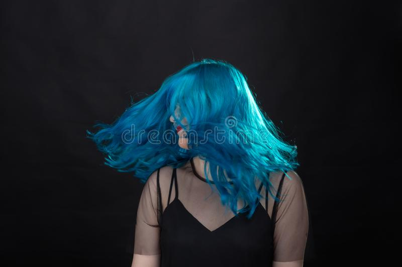 Style and fashion concept - Young and attractive woman with blue hair posing over black background royalty free stock image