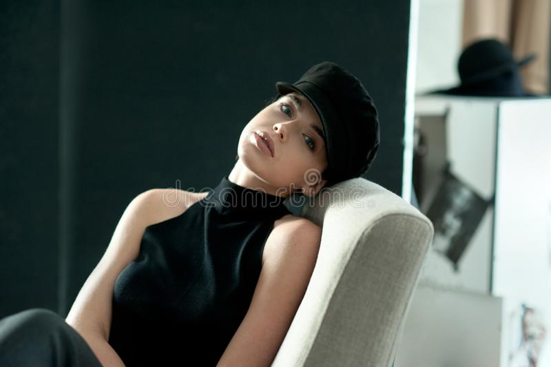 Style girl in black cap posed at studio on chair in interior. Style girl in black with cap posed at studio on chair in interior stock photo