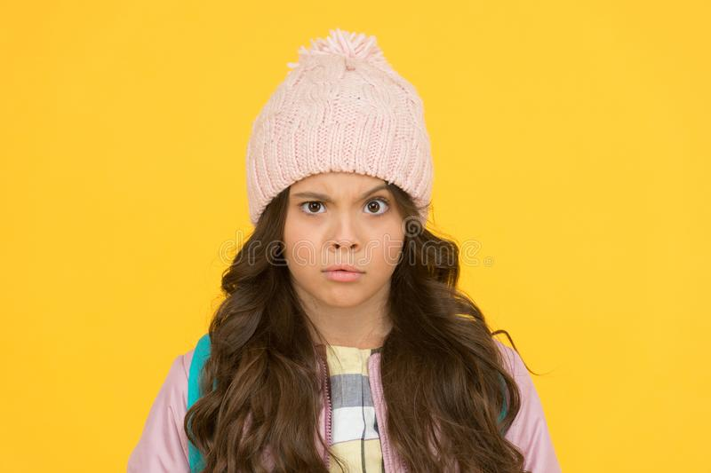 Style guide. Winter hat styles. Kid girl wear knitted hat. Winter accessory concept. Girl long hair yellow background. Cold season concept. Winter fashion stock photo
