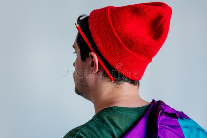 Style man in red hat and trendy clothes with pencil on ear. royalty free stock images