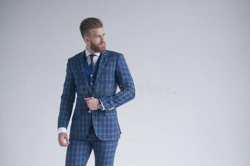Style in motion. Handsome young man in three-piece suit. posing in front of grey background. Style in motion. Handsome young man in full suit and sunglasses stock photos