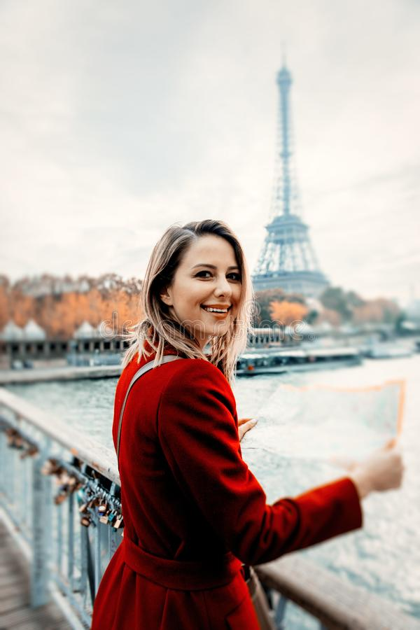 Girl in red coat with map at parisian street royalty free stock photos