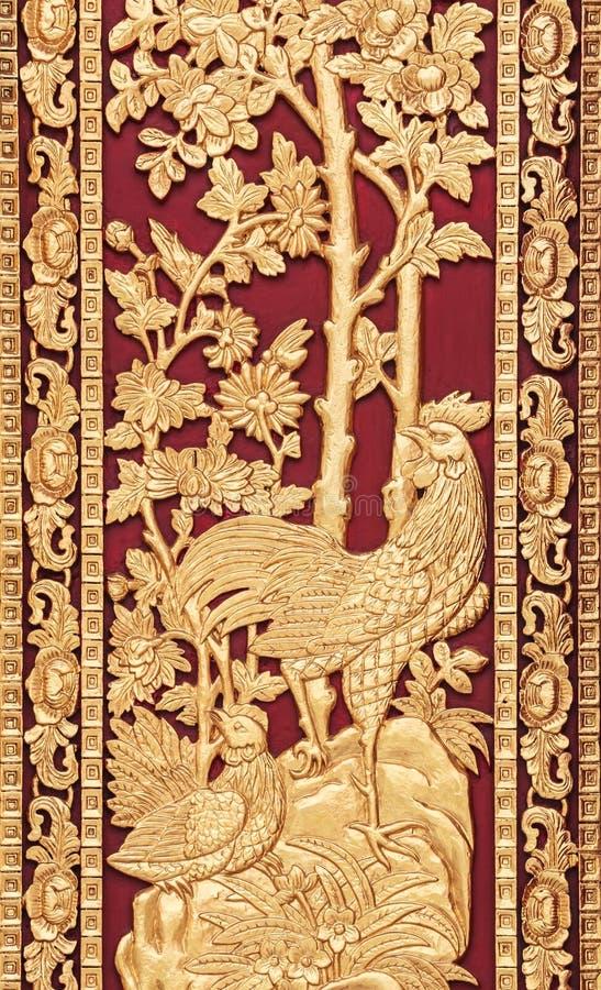 Style thaïlandais mythique découpant sur la porte en bois de temple photographie stock