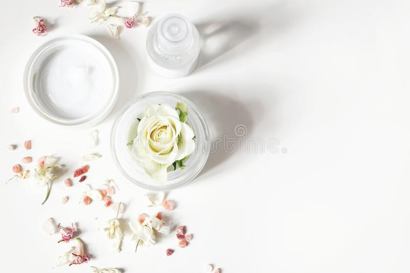Styled beauty composition. Skin cream, shampoo bottle, dry flowers, rose and Himalayan salt. White table background royalty free stock photo
