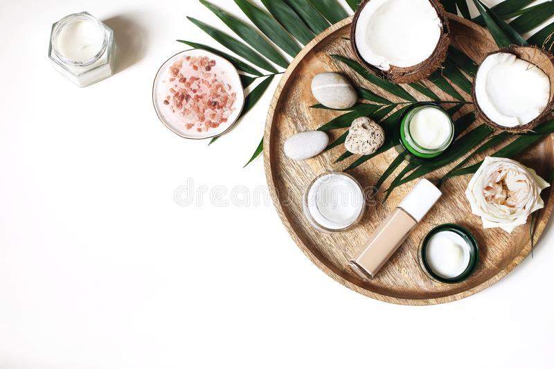 Styled beauty composition. Skin creams, makeup bottle, rose and pebble stones on wooden tray. Coconuts, tropical palm. Leaves decoration. Cosmetics, spa concept stock photo