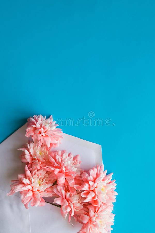 Styled feminine flat lay on blue candy background, top view.Minimal woman`s desktop with blank page mock up, envelope stock images