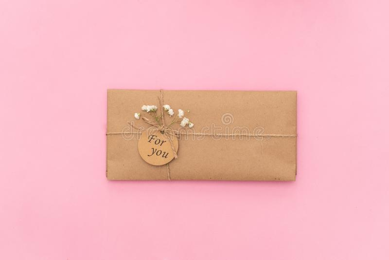Styled feminine flat lay on pale pastel pink background, top view. Minimal woman`s desktop with blank page mock up, open envelope and pink flower, Creative stock photography
