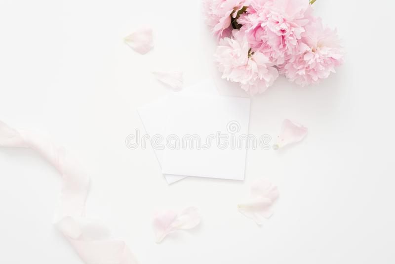 Styled feminine flat lay, white background, top view. Blank page mock up, envelope, peonies with petals, pink ribbon. royalty free stock photography