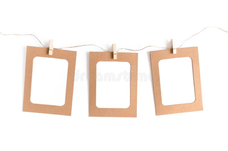 Styled minimal composition with kraft paper frame, wooden clothespins, twine rope stock photography