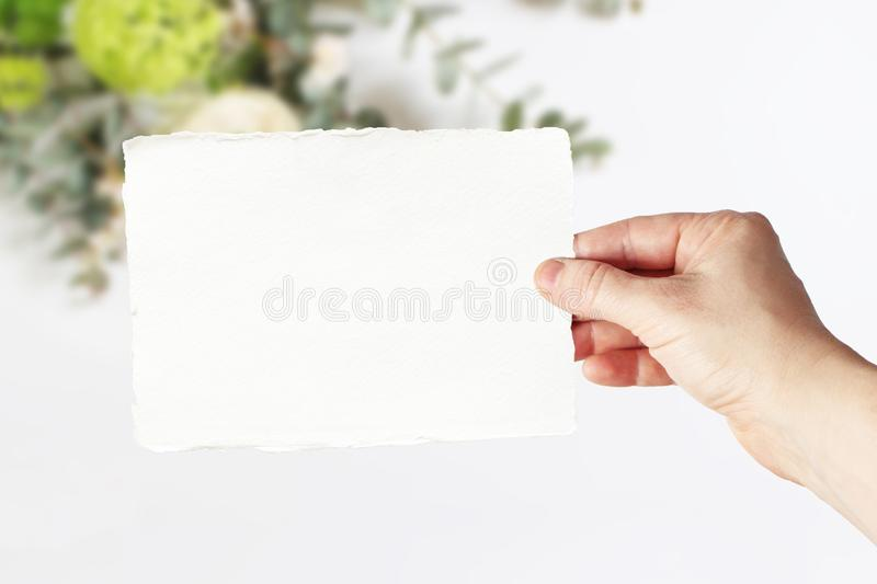 Styled stock photo. Feminine wedding, birthday greeting card mockup scene with woman`s hand in holding blank paper card royalty free stock photo