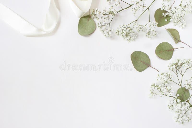 Styled stock photo. Feminine wedding desktop mockup with baby`s breath Gypsophila flowers, dry green eucalyptus leaves stock photography