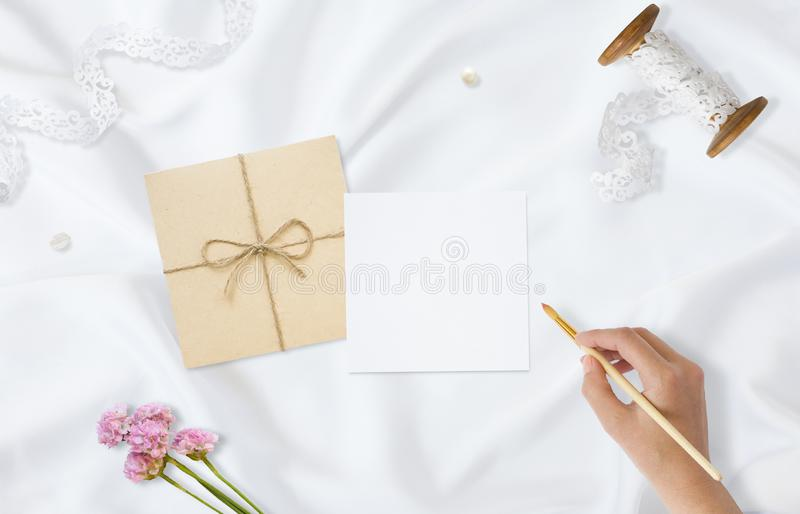 Styled stock photo. Feminine wedding desktop mockup. Greeting card. Flowers, paper, pen, tape on delicate satin stock image