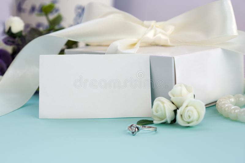 Styled stock photo. Feminine wedding desktop mockup. White roses, box with a bow, engagement ring, beads on pastel blue royalty free stock image