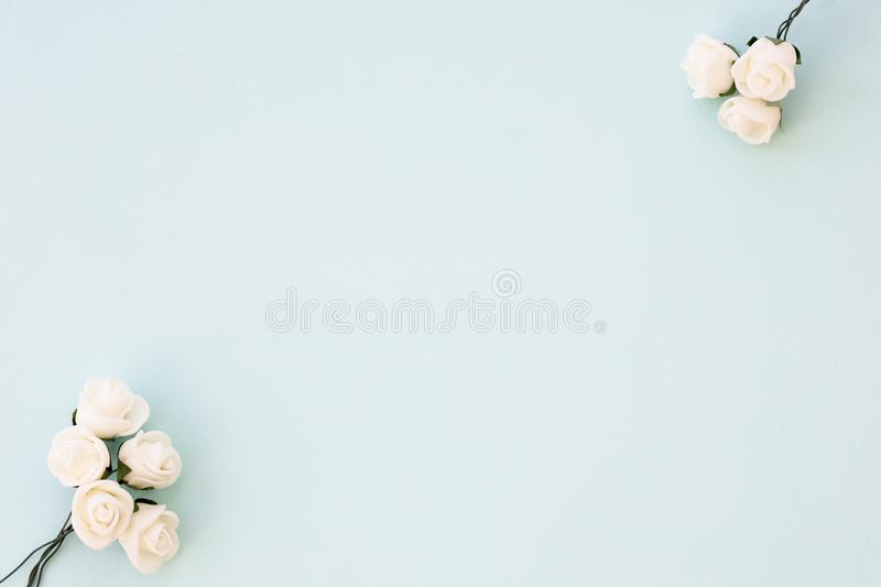 Styled stock photo. Feminine wedding desktop mockup. White roses on delicate blue background. Copy space. Top view. Picture for bl stock image