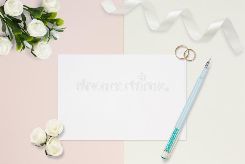 Styled stock photo. Feminine wedding desktop mockup. White roses, satin ribbon, beads on delicate beige background. Copy space. To royalty free stock photos