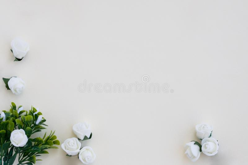 Styled stock photo. Feminine wedding desktop mockup. White roses, satin ribbon, beads on delicate beige background. Copy stock photography