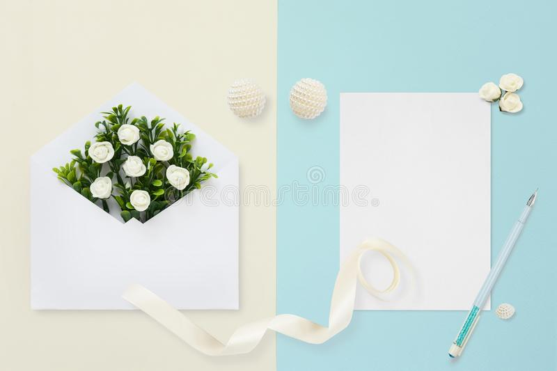 Styled stock photo. Feminine wedding desktop mockup. White roses, satin ribbon, beads on pastel beige blue background. Copy space. stock images