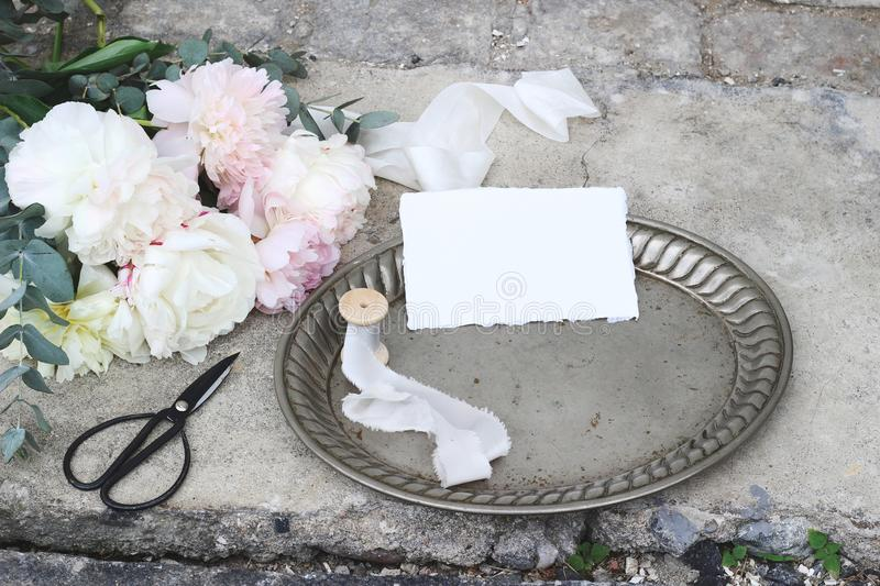 Styled stock photo. Feminine wedding still life composition with vintage silver tray, old scissors and silk ribbons royalty free stock photo