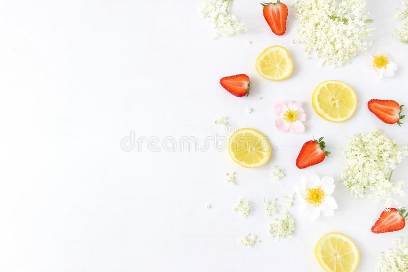 Styled stock photo. Spring or summer fruit composition. Sliced lemons, elderflowers, strawberries and wild roses. On white wooden table background, food pattern royalty free stock photos