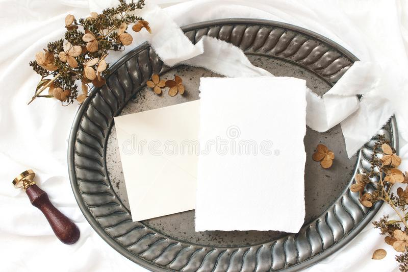 Styled stock photo. Winter, fall wedding, birthday table composition. Stationery mockup scene. Greeting card, envelope. Dry hydrangea flowers and ribbon on old royalty free stock photo