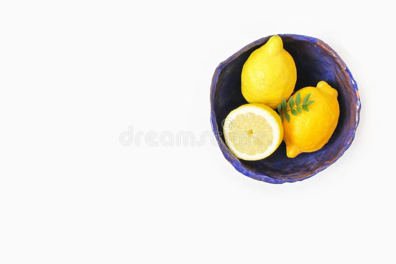 Styled stock photo. Yellow lemon fruit in decorative handmade cobalt blue ceramic bowl. Still life floral composition royalty free stock images