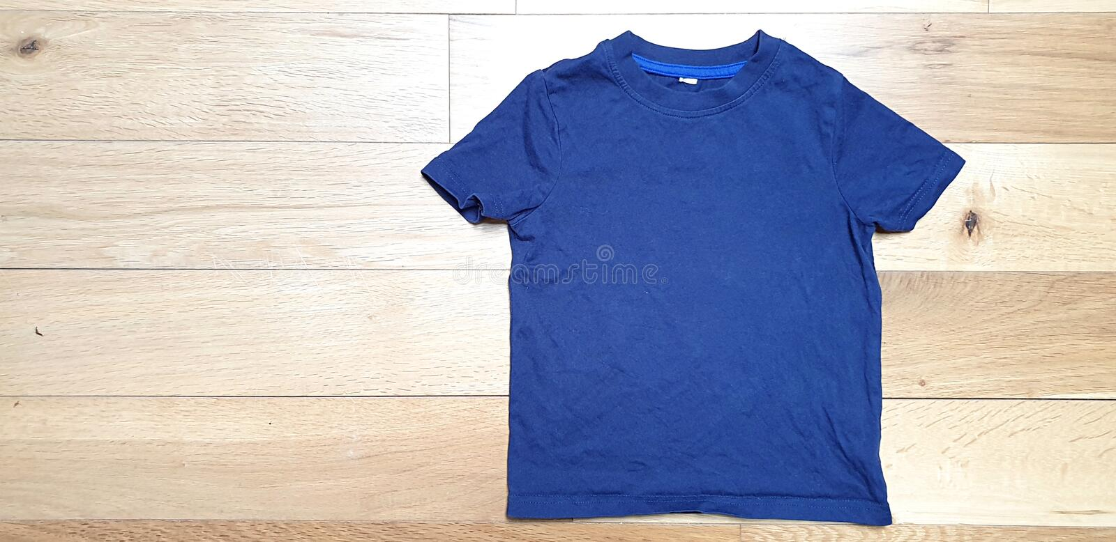 Styled Stock Photography, Mockup-Digital File, Blue toddler T-shirt Mock Up on light Wooded background. royalty free stock photography