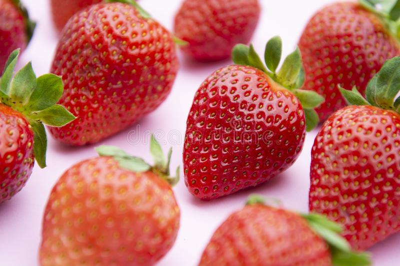Styled Strawberries background. Summer fresh berries over pink board stock photos