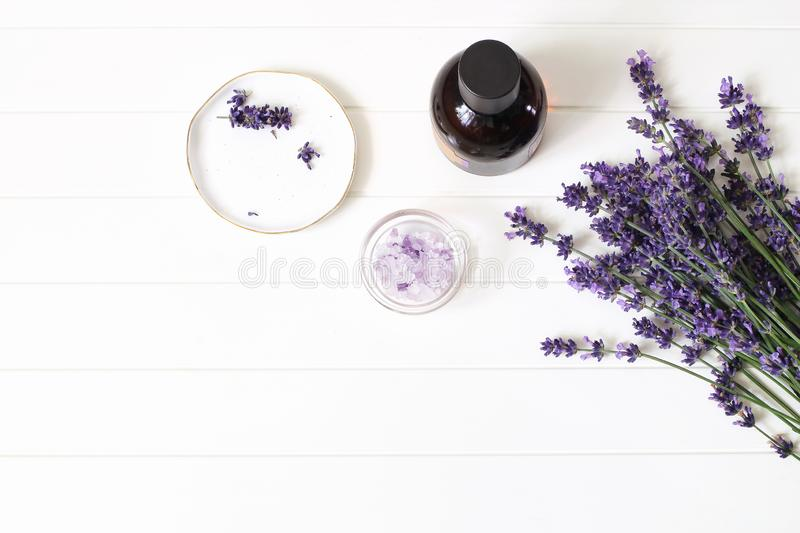 Styled summer beauty composition. Essential, massage oil, lavender flowers bouquet, bath salt on white wooden table royalty free stock images