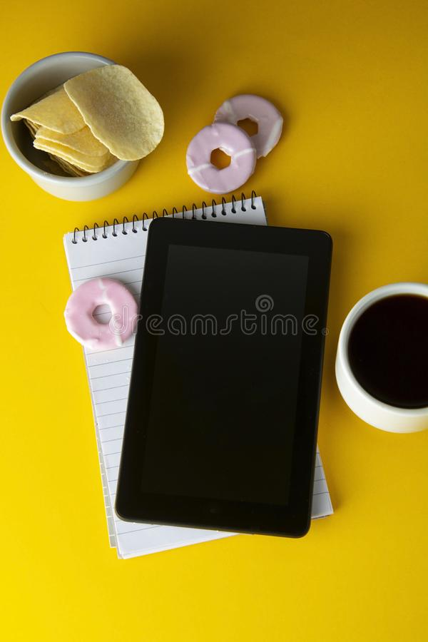 Styled yellow, food backdrop. Unhealthy lunch, snack with coffee, cookies, digital tablet. work space, lunch at work table. Top. View. Copy space eatting job royalty free stock photos