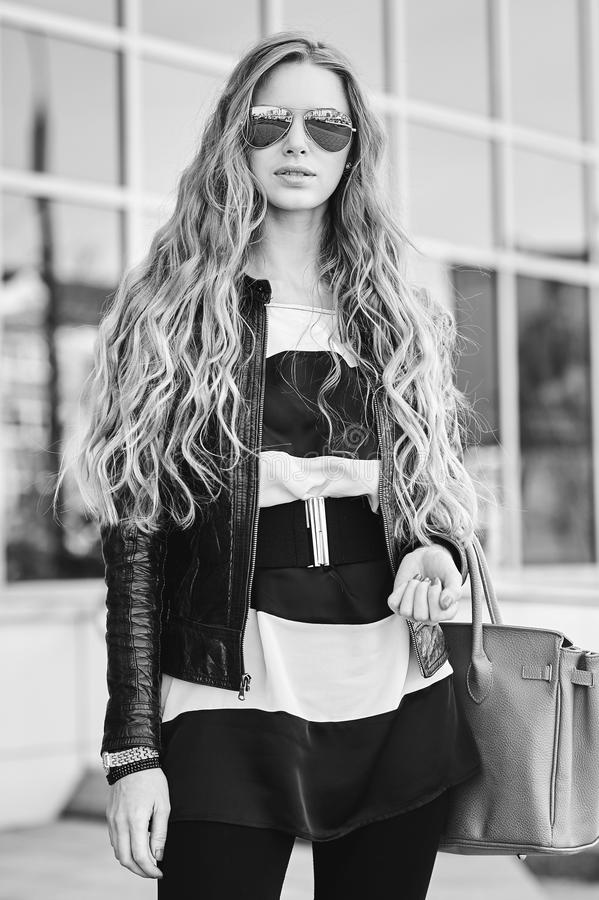 Styleish blond flicka med den utomhus- modeståenden för påse royaltyfri bild