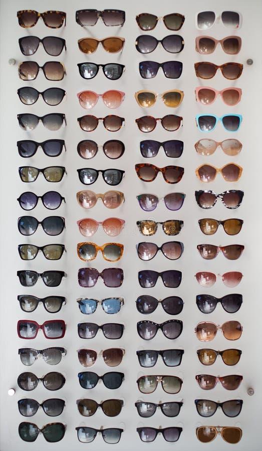 Styles assortis des lunettes de soleil teintées sur le fond blanc images stock